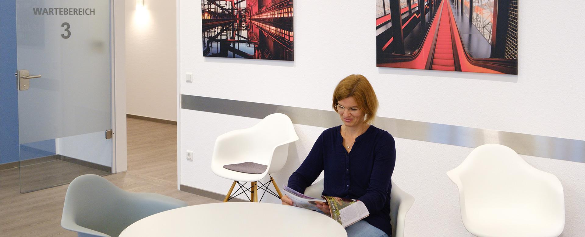 Frau im Wartezimmer liest Zeitung - Frauenarzt Frauenärztin Gynäkologie Pränataldiagnostik Essen